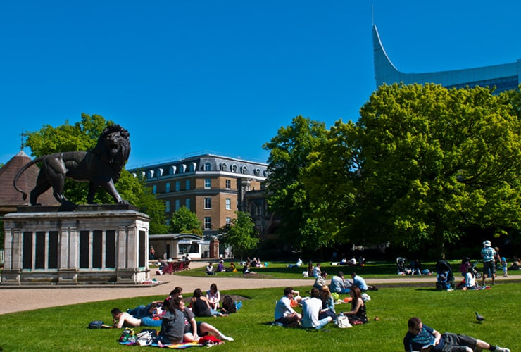 Groups of young people sat in a park on a summer day. Photograph taken in Forbury Gardens in Reading, UK.