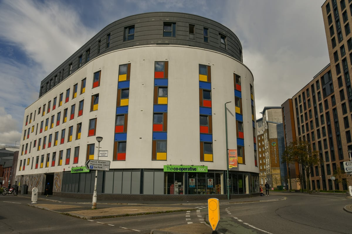 Colorful student accommodation building with a Co-operative food store in the ground floor.