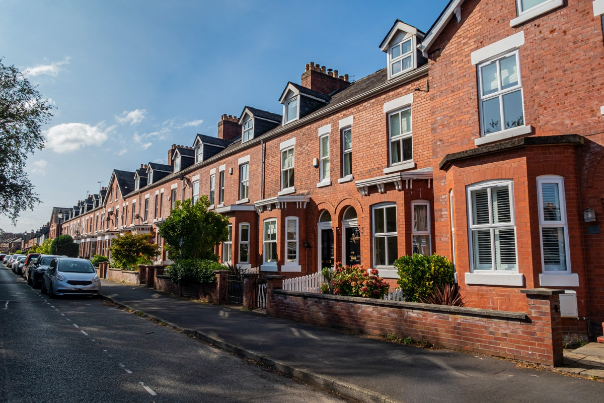 A typical residential street in Manchester with red-brick Georgian houses.