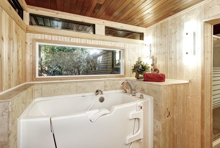 A walk-in bath in a wood-panelled bathroom.