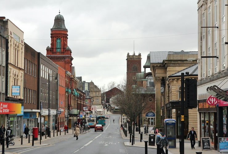 People visit a shopping street in Bolton, UK.