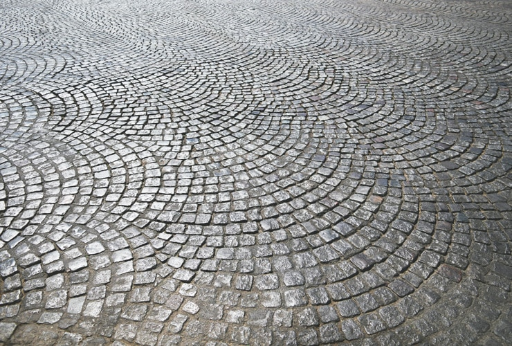 A close up of a patterned cobbled driveway.