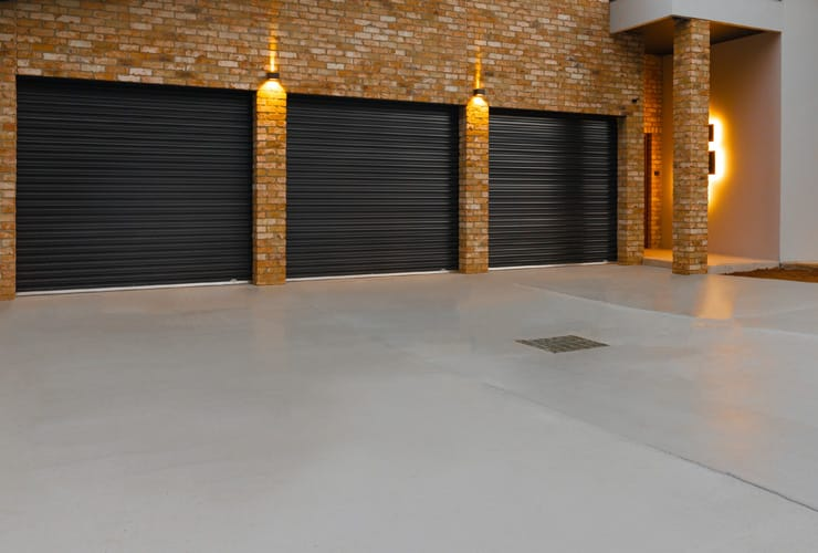 A freshley laid concrete driveway leads to three garage doors.