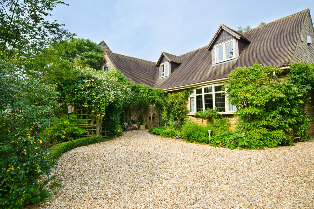 An English cottage with a gravel driveway.