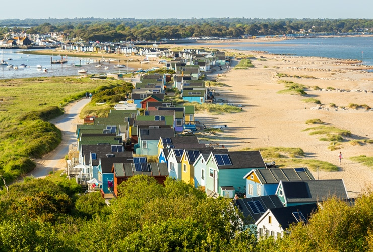 Colourful beach huts on the sand at Hengistbury Head in Bournemouth.