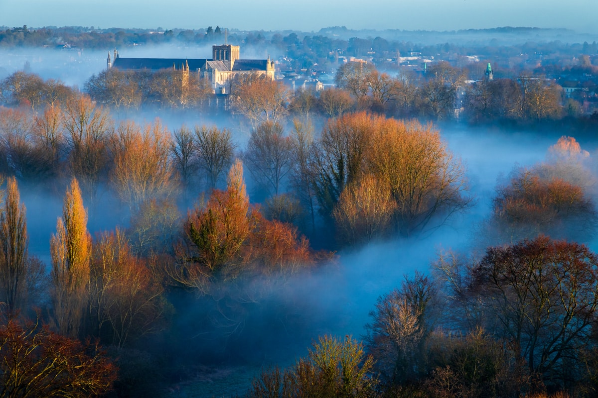 Winchester Cathedral in Hampshire, in the south downs, rises over mist in the early morning.