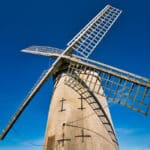 Bidston Windmill, on Bidston Hill in Birkenhead, Wirral, UK on a sunny day with a clear, blue sky. A sail casts a shadow across the structure of the mill which was built around 1800.