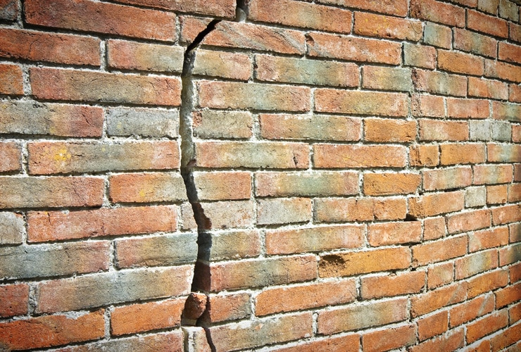 A deep crack in a brick wall.