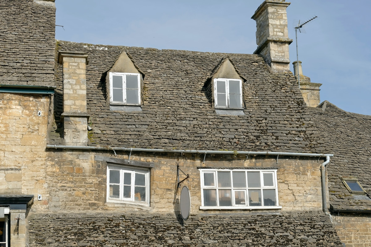 Subsidence damage visibile by the shape of the windows on an old house in the Cotswolds.