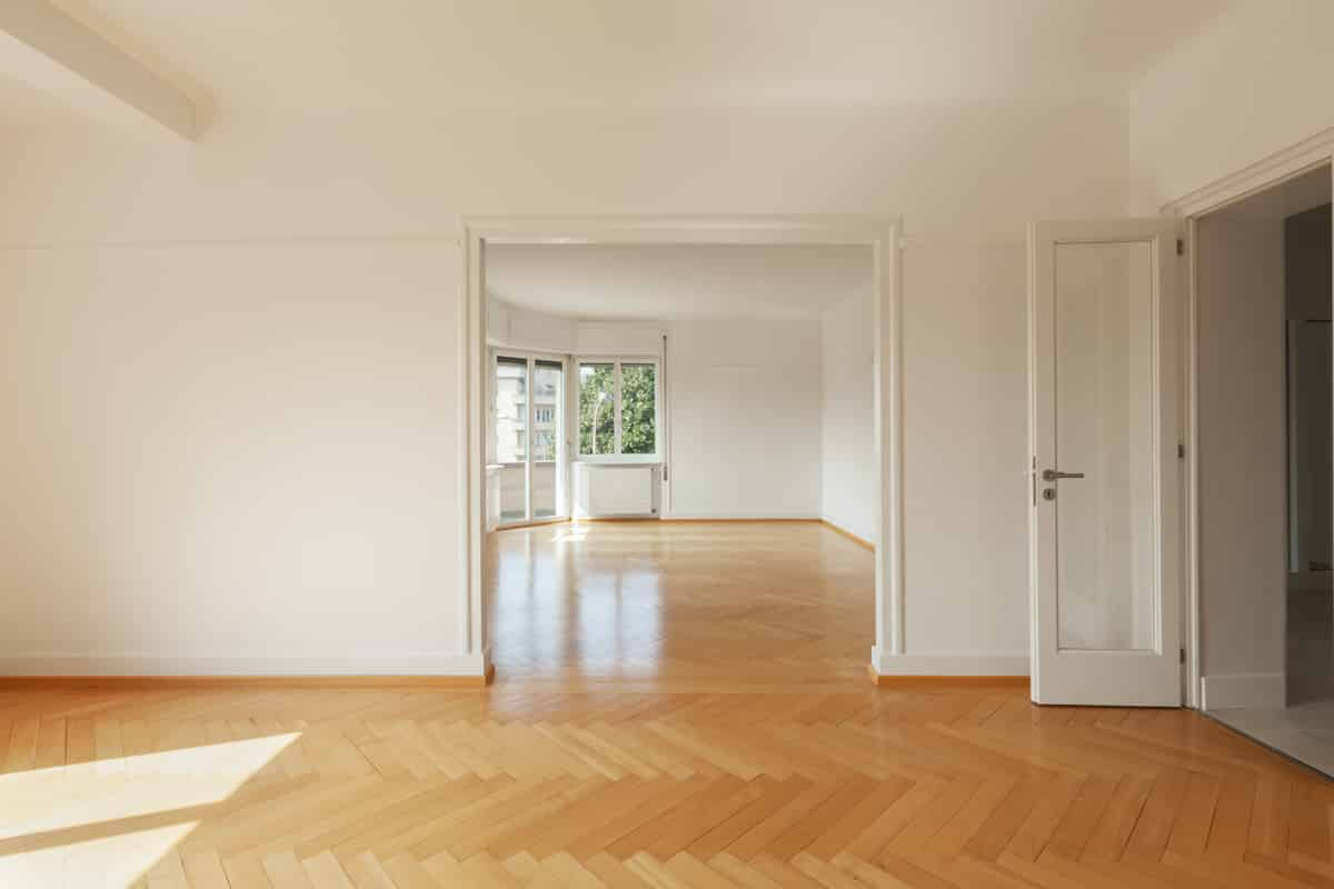 The interior of a modern apartment with wooden floors and completely empty and free of furniture.