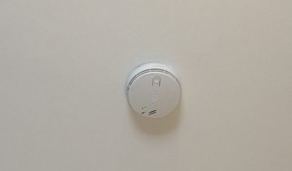 A mains wired fire alarm, fastened to a ceiling.